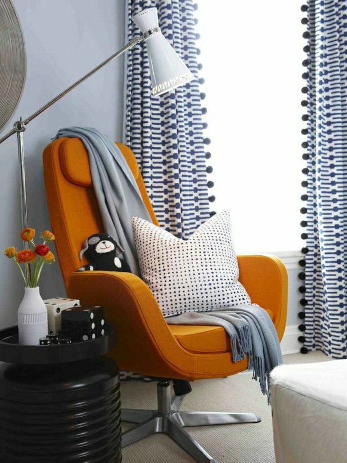 gemütliches-Wohnzimmer-orange-Sessel-graue-Schlafdecke-gepunktetes-Kissen-industrielle-Leselampe-Würfel-Plüschtier-moderne-Gardinen-blau-weiß