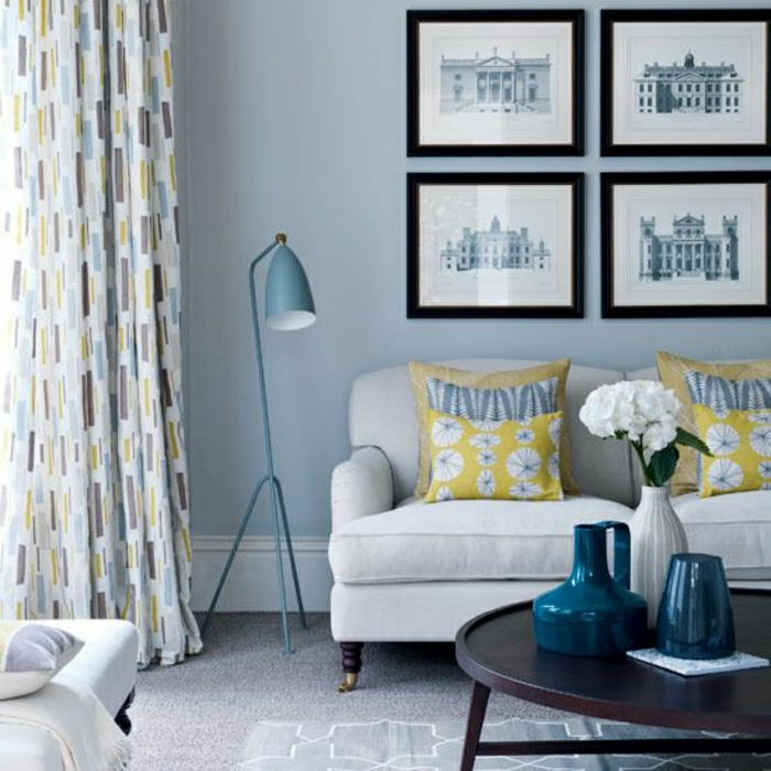 gemütliches-Wohnzimmer-stilvolle-Gestaltung-Bilder-Sofa-industrielle-Stehlampe-Gardinen-blau-grau-gelb