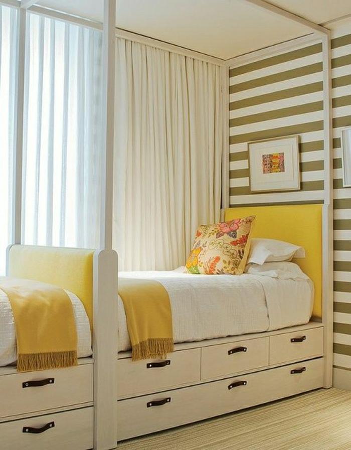 gestreifte-Wände-gelbe-Betten-Schubladen-Schlafdecken-bunte-Kisse-Bild-weiße-Gardinen