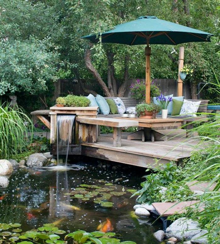 grüner-Gartenschirm-Gartenmöbel-Holz-viele-Kissen-kleiner-Wasserfall