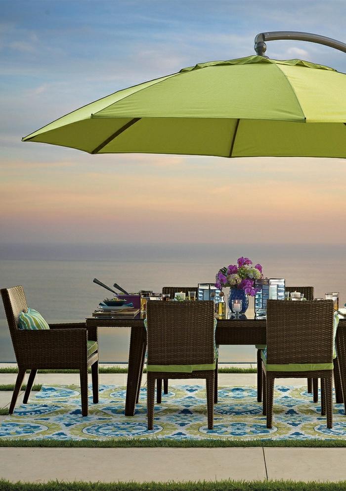 grüner-Gartenschirm-Tisch-Stühle-Rattan-Blumen-Meer-Sonnenuntergang