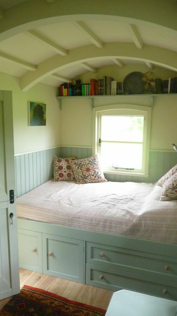 grünes-Schlafzimmer-Bett-Minze-Farbe-Schubladen-bunte-Kissen-Bücherregal