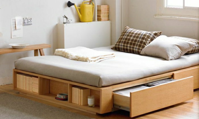 hölzernes-Bett-Schubladen-weiße-Wände-beige-Bettwäsche-Bücher-minimalistisch