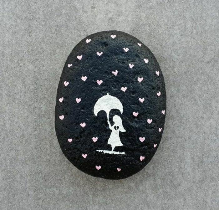handgemalter-Stein-schwarze-Grundlage-weiße-Zeichnung-kleines-Mädchen-Regenschirm-Regentropfen-Herzen