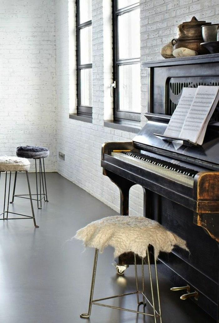 moderne-Wohnung-weiße-Ziegelwände-altes-vintage-Klavier-drei-Hocker-Notenblätter