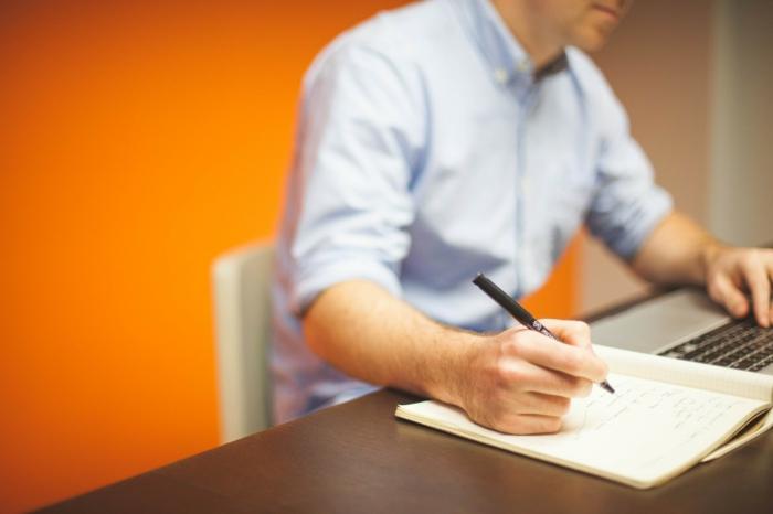 moderne-bürolandschaften-ein-mann-schreibt-auf-einem-bürotisch