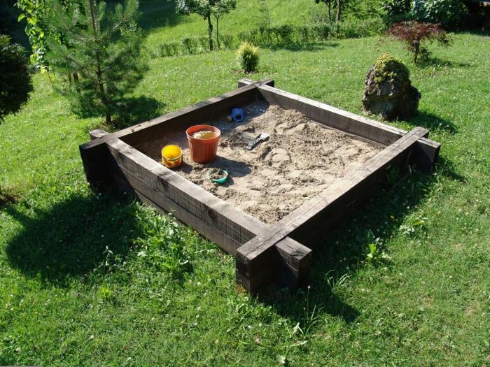 sandkasten-aus-holz-modell-mit-vier-ecken-auf-dem-gras