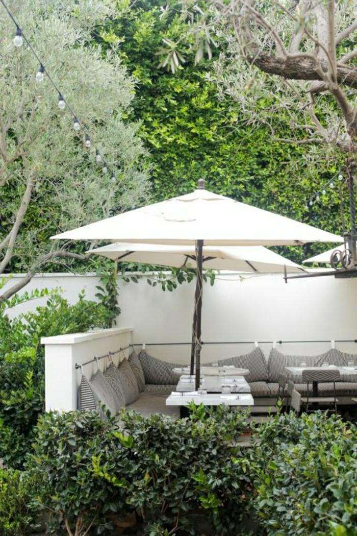 weiße-Gartenschirme-Leine-Leuchten-Bänke-graue-Kissen