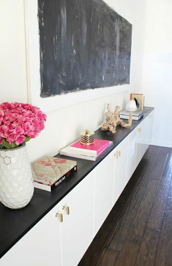 weißer-Schrank-Bücher-Souveniers-rosige-Blumen-schwarze-Tafel-Wanddeko