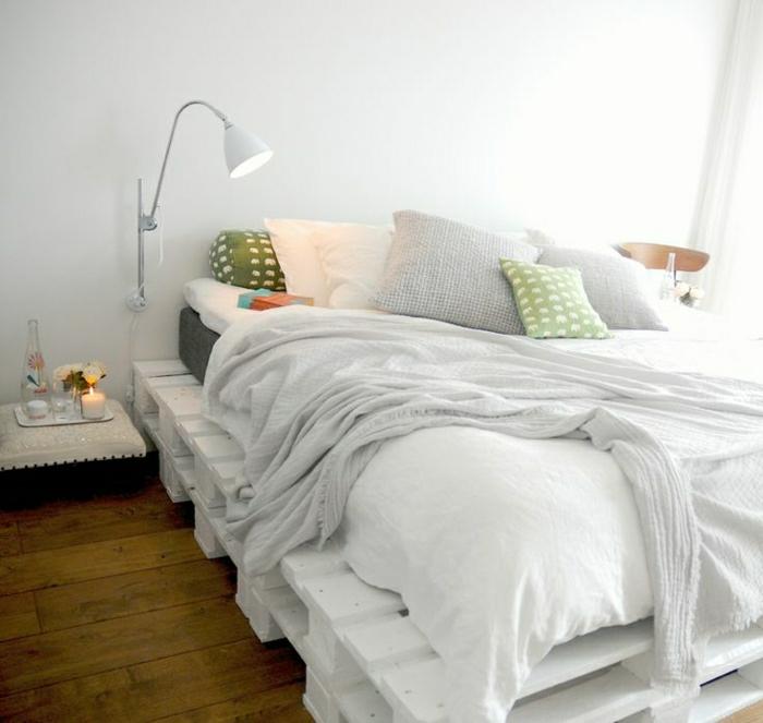 Bett-aus-Paletten-weiß-Kissen-lustiges-Muster-Leselampe-weiße-Bettwäsche