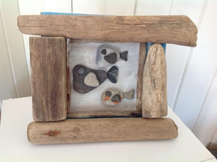 Rahmen aus Treibholz und Fische aus … Steinen