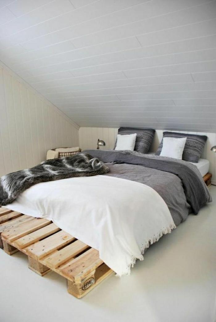 Dachwohnung-minimalistisches-Interieur-europaletten-bett-graue-Bettwäsche-weiße-Schlafdecke