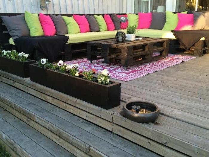 Garten-Veranda-Gestaltung-Ecksofa-Paletten-Kissen-grelle-Farben-Teppich-Couchtisch-Blumen-Kästen