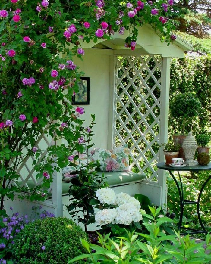 Gartenbank-mit-Dach-weiß-Dach-Gitterwände-Blumen-Kissen-Tisch-Blumentöpfe