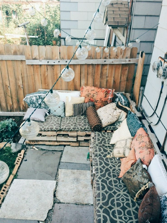 Gartenmöbel-Gartengestaltung-Sofa-aus-Paletten-Kissen-hängende-Leuchten-Zaun