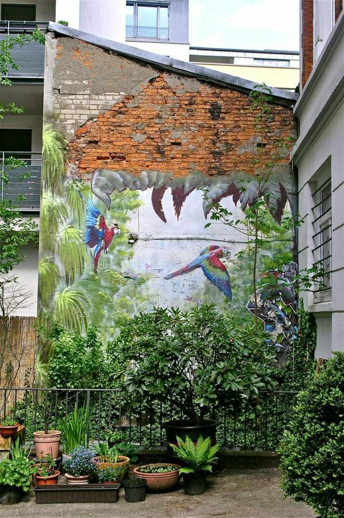 Gebäude-Ziegelwand-Graffiti-Bilder-Pflanzen-Palmen-Papageien-exotisch