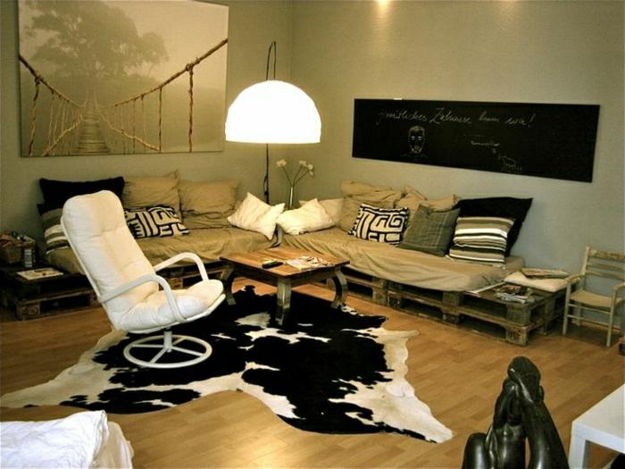 Palleten-Sofa-beige-viele-Kissen-Leder-Sessel-weiß-Tierhaut-afrikanische-Statue-schwarze-Tafel-großes-Bild