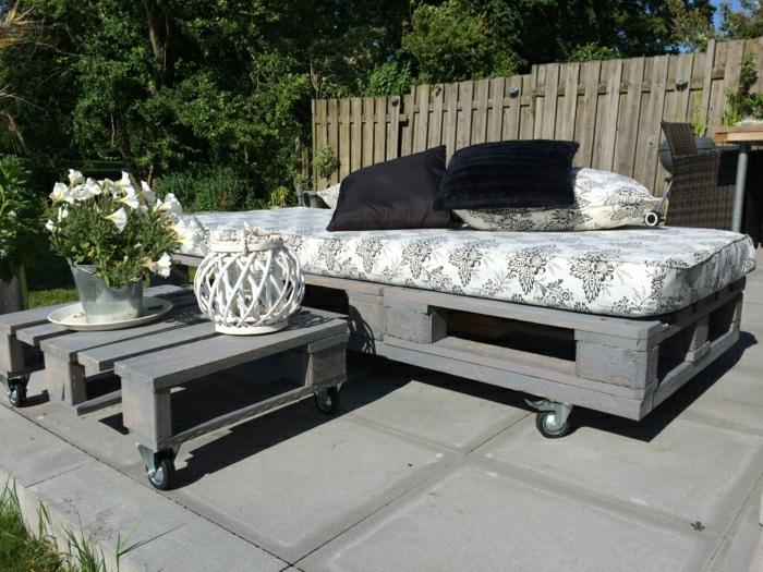 Patio-Gestaltung-graue-Palettenmöbel-Rollen-schöne-Matraze-schwarze-Kissen-Blumen