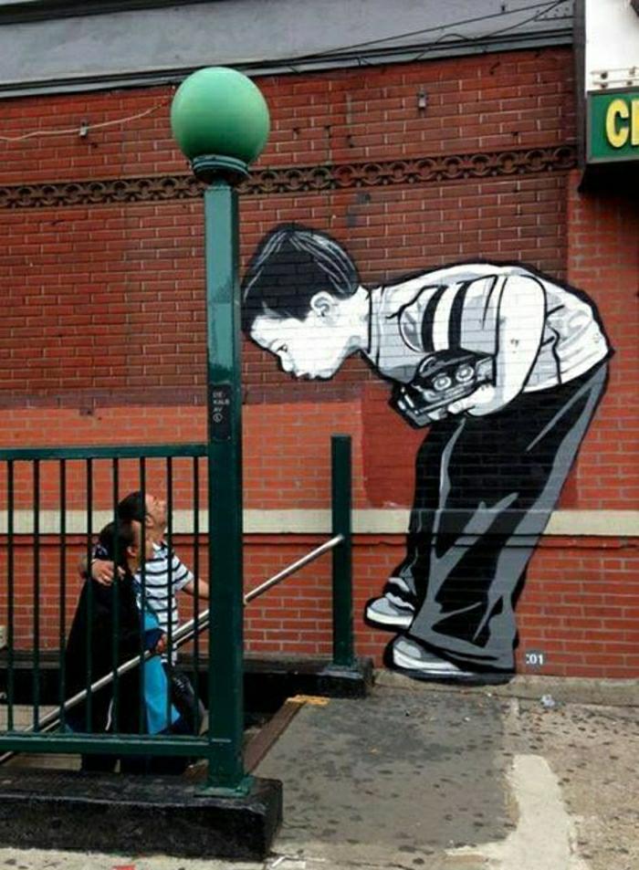 Schablonengraffiti-kleiner-Junge-neuguerig-Leute-Metro-Ziegelgebäude