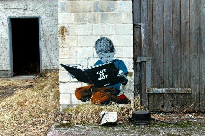 Scheune-Ziegelwand-Graffiti-Junge-Buch-lesend