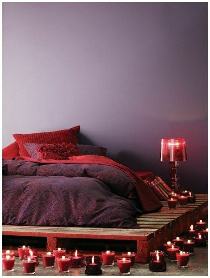 Schlafzimmer-attraktiv-lila-Bettwäsche-rote-Kissen-Kerzen-Nachttischlampe-Paletten-Rahmen-Bett
