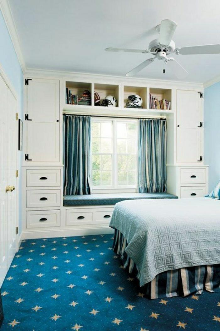 Schlafzimmer-elegante-Gestaltung-blauer-Teppich-Bettwäsche-Gardinen-kleines-Fenszter-weißer-Kleiderschrank