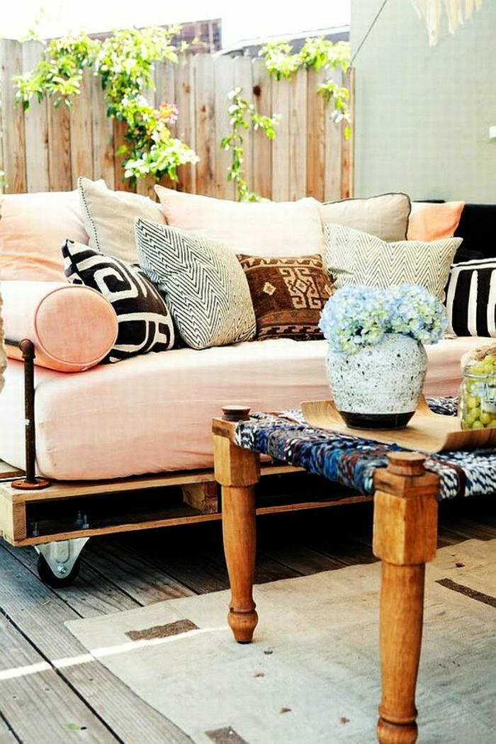 Sofa-aus-Paletten-Rollen-Kissen-Couchtisch-Vase-Gartenmöbel