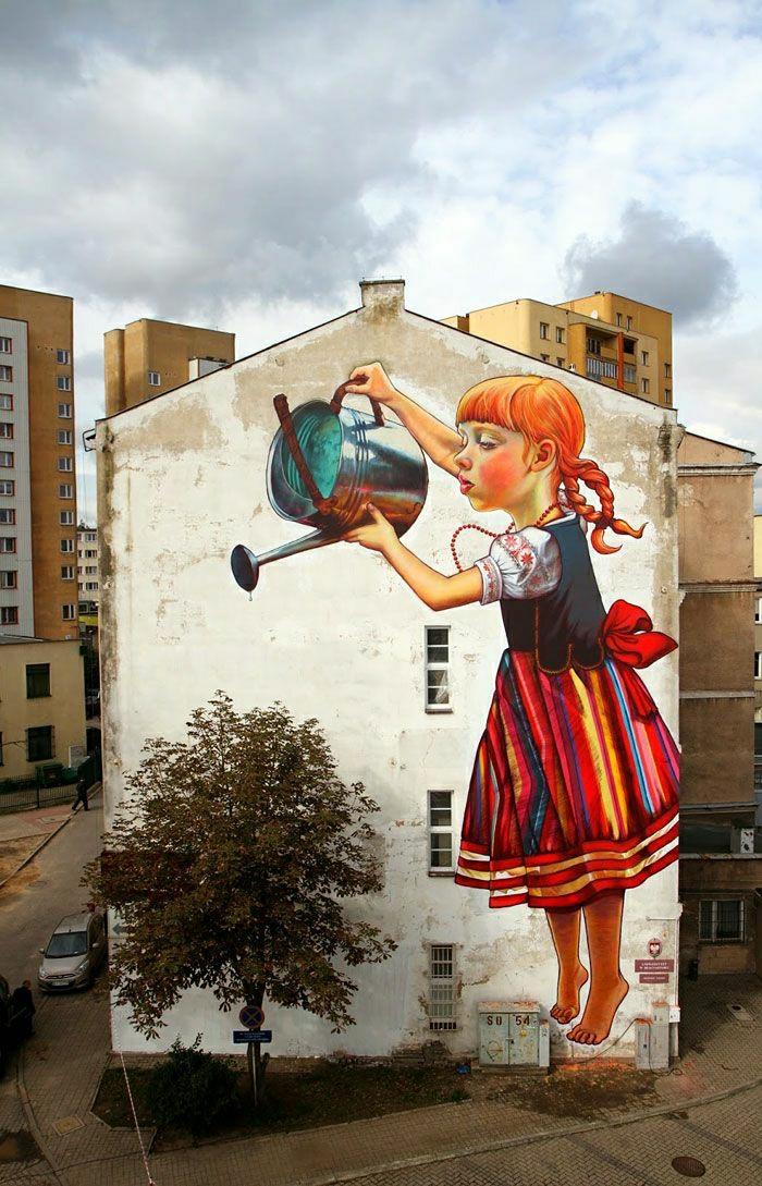 Wohngebäude-Graffiti-Bilder-Mädchen-Volkstracht-Gießkanne-Baum