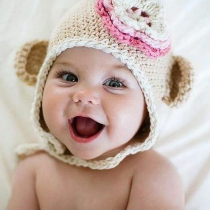 lächelndes baby mit einem handgestrickten hut