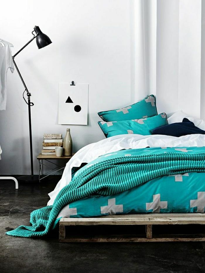 bett-aus-europaletten-selber-bauen-Bettwäsche-Schlafdecke-Minze-Farbe-Stehlampe-Zeichnung-geometrische-Figuren-Nachttisch-Flasche-Tasse-Bücher
