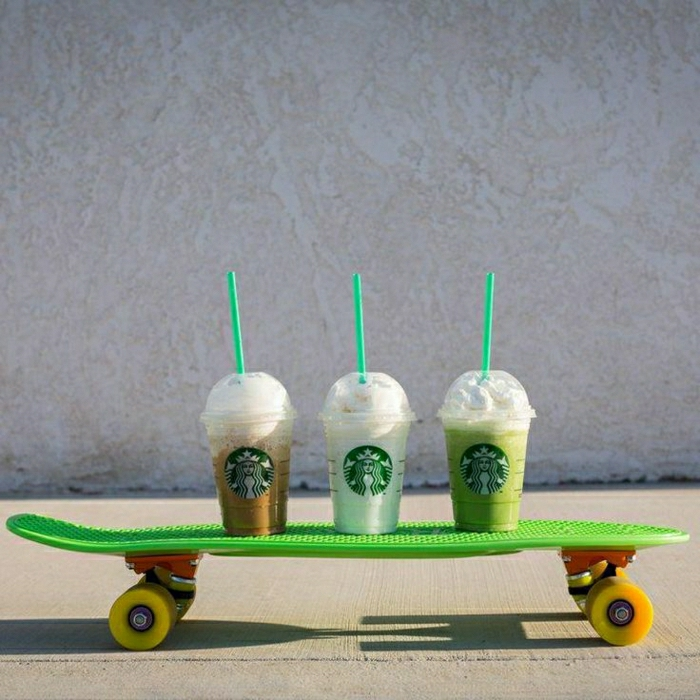 drei-Starbucks-Becher-verschiedene-Getränke-Strohe-Rollbrett
