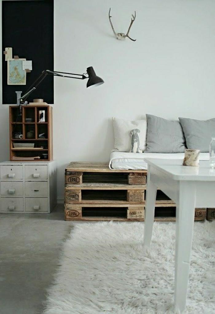 gemütiches-Zimmer-skandinavischer-EInrichtungsstil-rustikale-Elemente-weißer-Esstisch-Paletten-Sofa-weiße-graue-Kissen-Schubladen-Leselampe-Geweih-flaumiger-Teppich