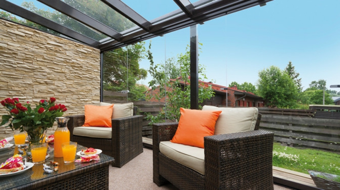 glasswand-terrasse-orange-dekokissen-auf-den-sesseln