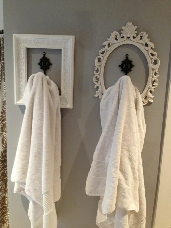 graue-Wand-schwarze-Kleiderhaken-weiße-Barock-Bilderrahmen-Tücher