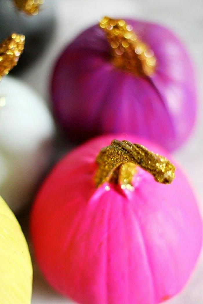 lackierte-Kürbisse-grelle-Farben-goldene-Stiele-frische-Dekorationsidee