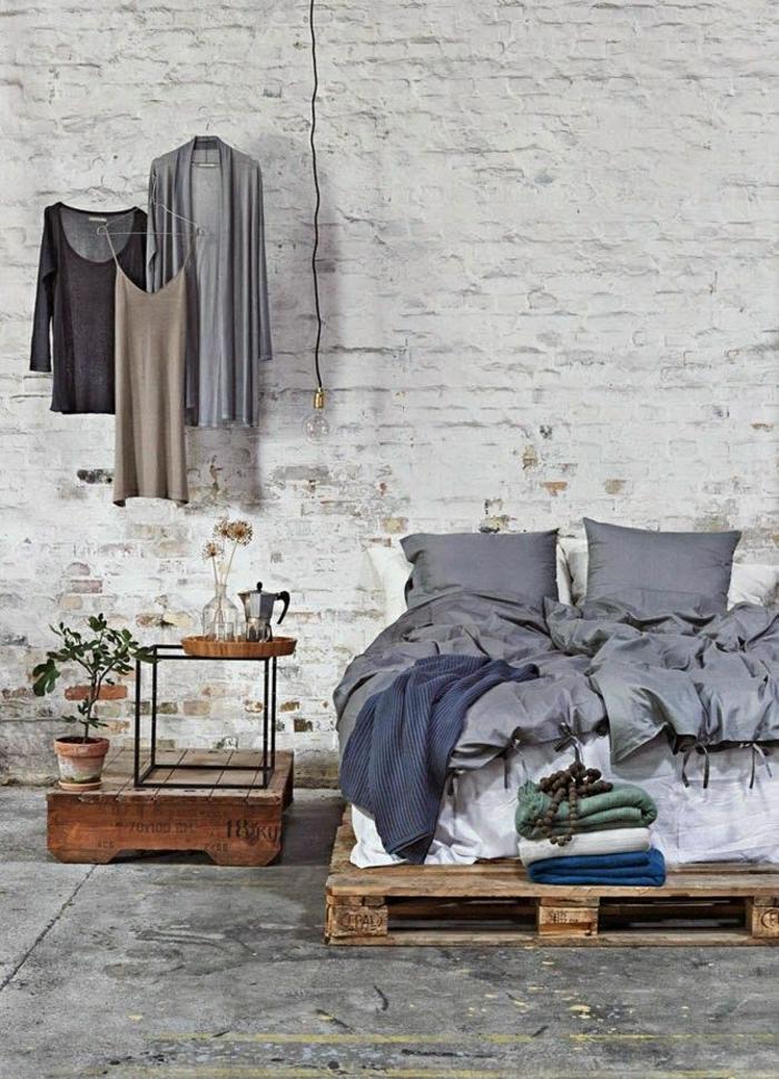 möbel-aus-paletten-bett-selber-bauen-Nachttisch-Topfpflanze-graue-Bettwäsche-hängende-Kleider-Leuchte-Glühbirne