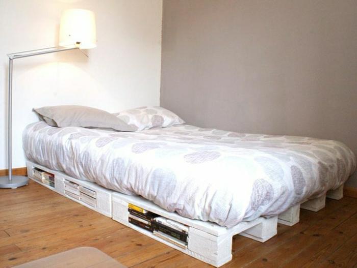 möbel-aus-paletten-weißes-Bett-Speicher-Bücher-Bettwäsche-Runden-graues-Kissen-Stehlampe-minimalistisches-Interieur