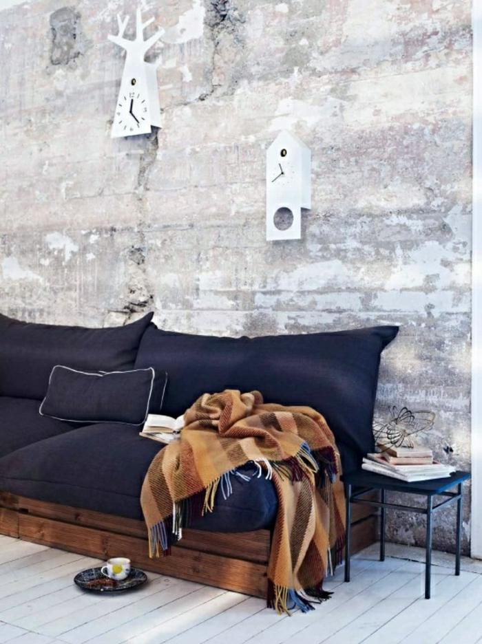 minimalistisches-Interieur-räumliches-Zimmer-Paletten-Couch-blaue-Polster-vintage-Schlafdecke-Wanduhren-Ziegelwände