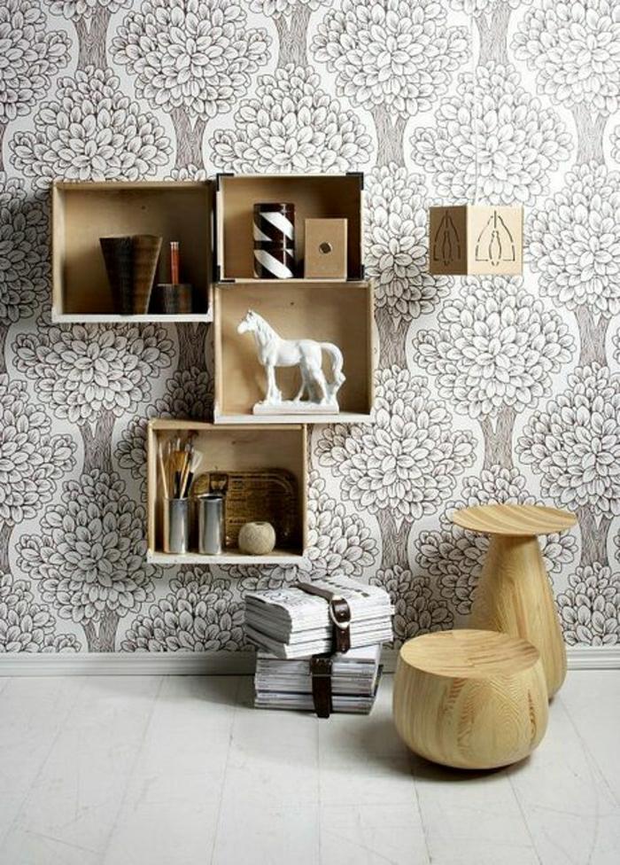skandinavisches-Interieur-weinkisten-holz-Regale-Figuren-Souvenirs-Vasen-schwarz-weiße-Tapeten-hölzerne-Hocker-Zeitungen