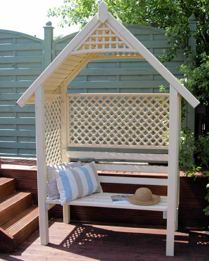 weiße-Gartenbank-mit-Dach-Gitter-Kissen-Strohhut-Zeitschrift