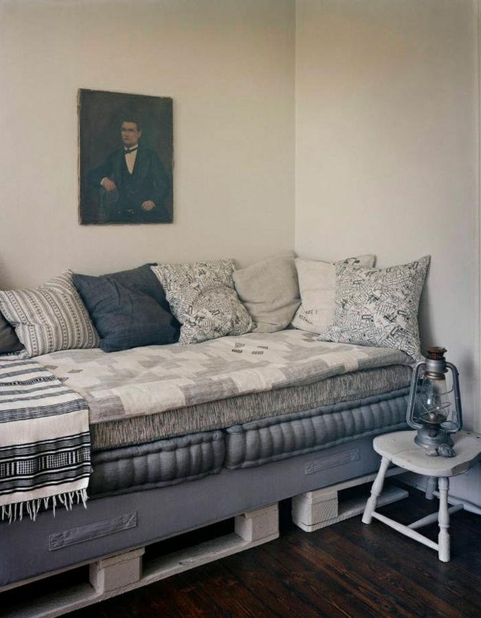 weiße-Paletten-Sofa-Matraze-blaue-Polster-schöne-Kissen-Porträt-Laterne-stilvolles-Interieur