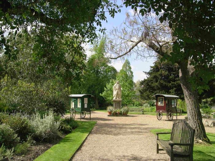 Chelsea-Physic-Garden-aristokratisch-historisch-Statue-dekorative-Steine-Alleen-Bäume-hölzerne-Bank-Büsche-retro-Kutschen-englischer-Garten