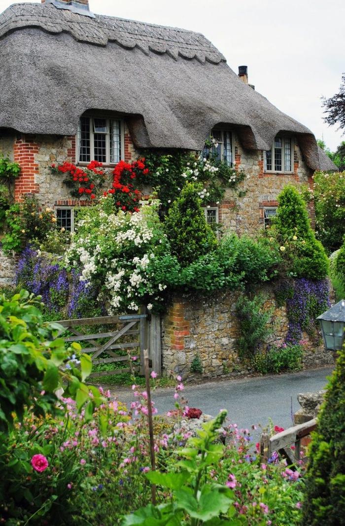 Haus-Stein-Ziegen-schleichende-Blumen-englischer-Landgarten