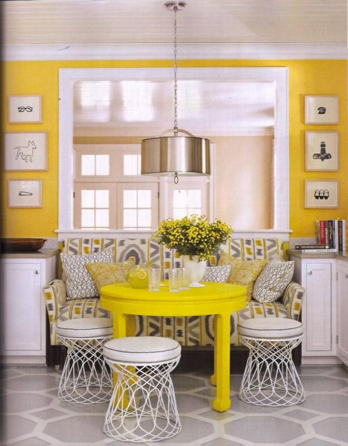 Küche-gelbes-Interieur-süßer-Tisch-kleine-Couch-buntes-Muster-graphische-Kissen-Gläser-gelbe-Blumen-Hocker