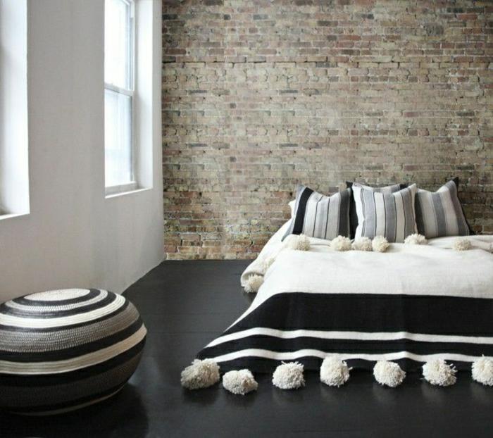 Schlafzimmer-Ziegelwände-minimalistische-Einrichtung-marokkanischer-Pom-Pom-Bettüberwurf-schwarz-weiß-grau