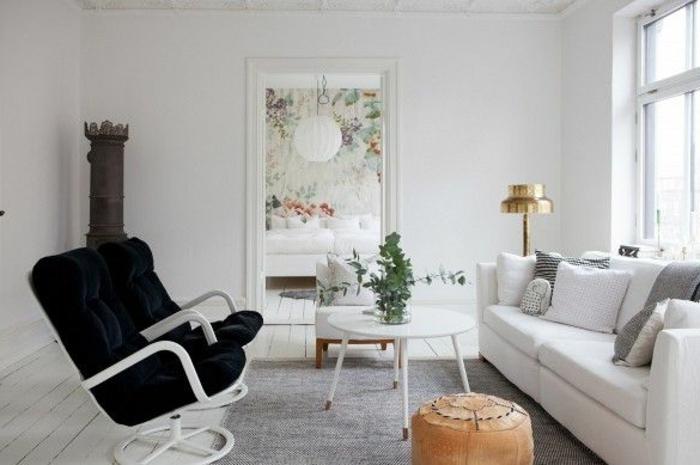 Wohnzimmer-skandinavischer-EInrichtungsstil-schwarz-weiß-bequemes-Sofa-runder-Couchtisch-weiß-Hocker-schwarze-Sessel