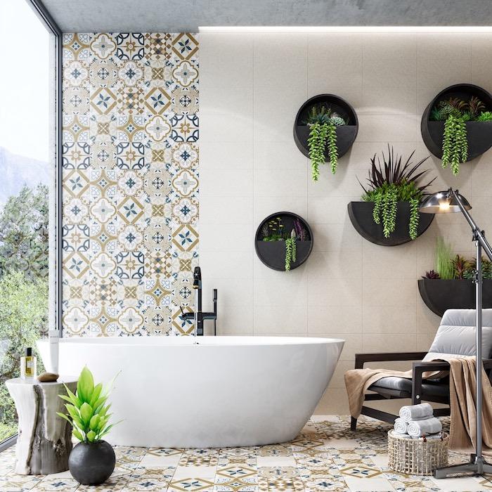 Badezimmer Fliesen in marokkanischem Stil, weiße Badewanne aus Keramik, schwarze Blumentöpfe an der Wand