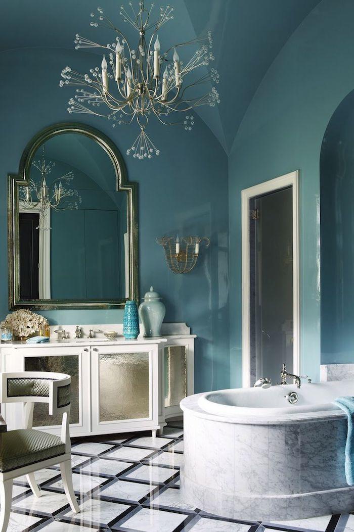 Moderne Bäder, verspielter Kronleuchter, Badewanne aus Marmor, abgerundeter Spiegel, Wandfarbe Blau