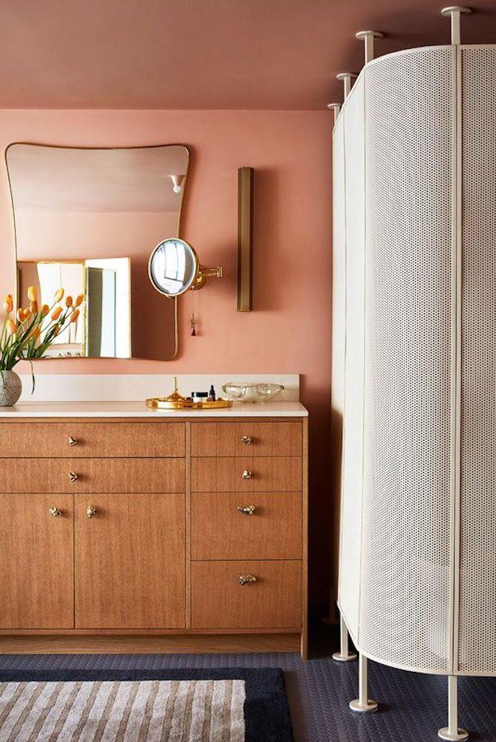 Bad Einrichtung modern, Wandfarbe Rosa, abgerundeter Spiegel, Holzschrank und Duschkabine aus Metall