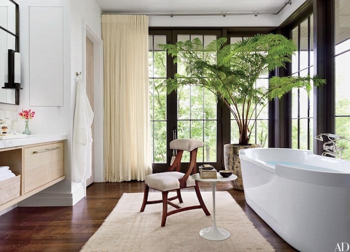 Luxus Bad Einrichtung, dunkler Holzboden, weiße Keramik Badewanne, großer Fenster, Grünpflanze in Blumentopf